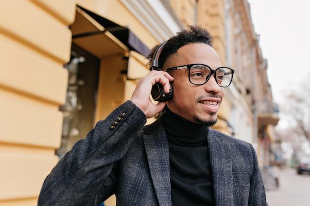 Błogi amerykanin słuchający muzyki podczas spaceru po mieście. afrykański młody człowiek spędza czas na świeżym powietrzu, ciesząc się ulubionymi piosenkami w słuchawkach.
