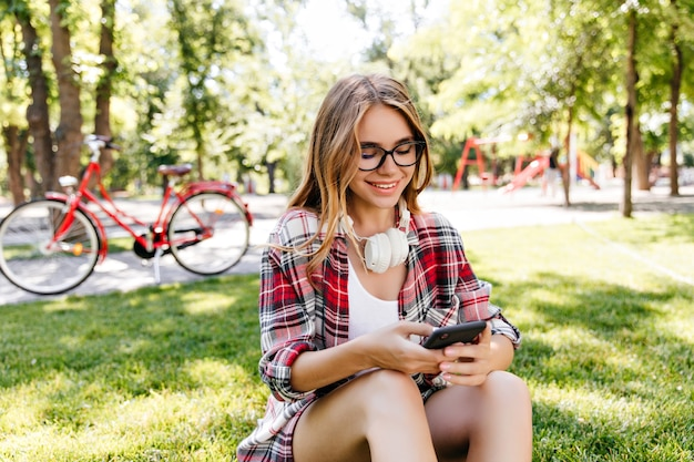 Błogi biała dama przy użyciu telefonu w parku. radosna europejska dziewczyna w dorywczo okularach siedzi na trawie i sms-y wiadomości.