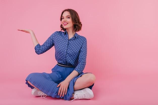 Błogi brunet dziewczyna siedzi na podłodze i uśmiecha się. szczęśliwa brunetka kobieta nosi niebieską spódnicę i bluzkę.