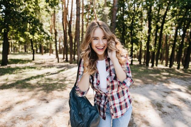 Błogi kręcone kobieta pozuje z telefonem w parku lato i śmiejąc się. dobrze ubrana kaukaska dziewczyna wyrażająca szczere pozytywne emocje.
