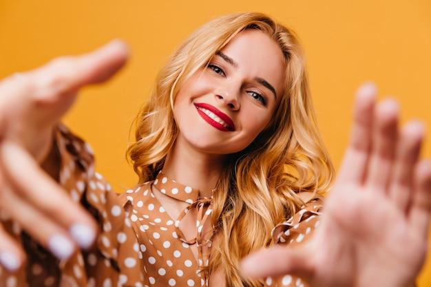 Błogi młoda kobieta pozuje z zainteresowanym uśmiechem. kryty strzał eleganckiej białej modelki, pozowanie na żółtej ścianie.