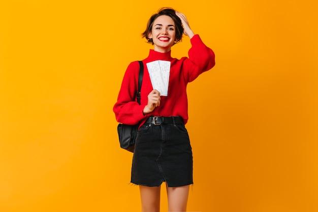 Błogi turysta kobieta w czerwonym swetrze trzyma bilety