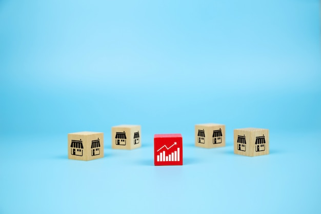 Blogi z drewnianymi zabawkami cube z ikoną sklepu marketingowego franczyzy i ikoną wykresu dla rozwoju firmy.