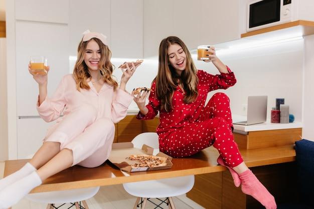 Błogie europejskie dziewczyny wyrażające pozytywne emocje przy porannym piciu soku. kaukaskie panie w piżamie śmieją się jedząc pizzę podczas śniadania.