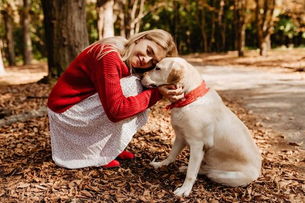 Błogo szczęśliwa blondynka uśmiechając się blisko swojego psa. piękna kobieta czuje się szczęśliwa z ukochanym zwierzakiem.