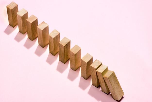 Blok domino. domino ciągle przewracane na różowym tle.
