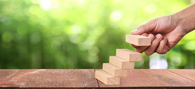 Blok drewna w dłoni sztaplowania jako schodek. wzrost koncepcji biznesowej