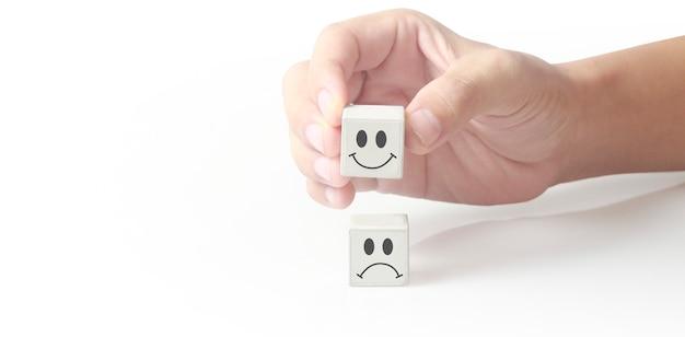 Blok kostki w ręku z ikoną radosnej i smutnej twarzy