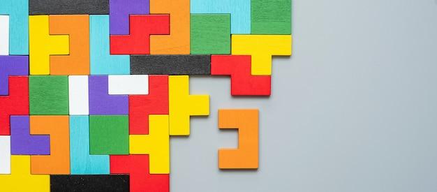 Blok o geometrycznym kształcie z kolorowym drewnianym puzzlem.