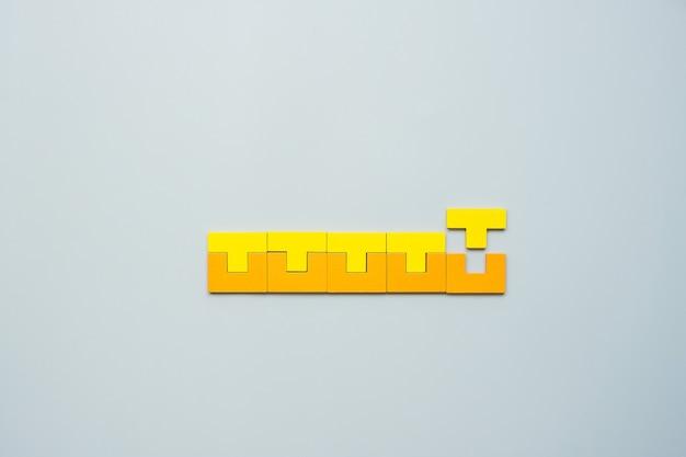 Blok o geometrycznym kształcie z kolorowymi drewnianymi puzzlami.