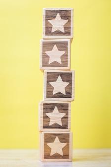 Blok symbol gwiazdy na żółtym tle. ocena usług, ranking, ocena klientów, satysfakcja, ocena i koncepcja informacji zwrotnych
