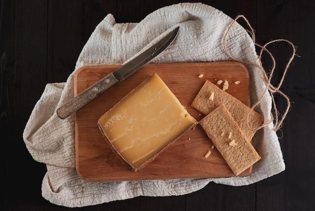 Blok szwajcarskiego twardego sera na desce do krojenia z nożem i pieczywem chrupkim na ciemnym tle drewnianych