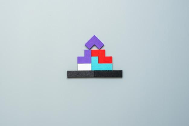 Blok w kształcie domu z kolorowymi drewnianymi puzzlami na szaro. logiczne myślenie, logika biznesowa, rozwiązania, koncepcje racjonalne, dom, nieruchomości i strategie