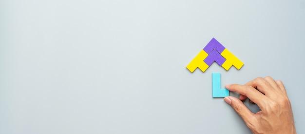 Blok w kształcie parasola z kolorowego drewnianego kawałka układanki na szaro.