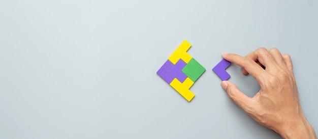 Blok w kształcie ryby z kolorowego drewnianego kawałka układanki na szaro.