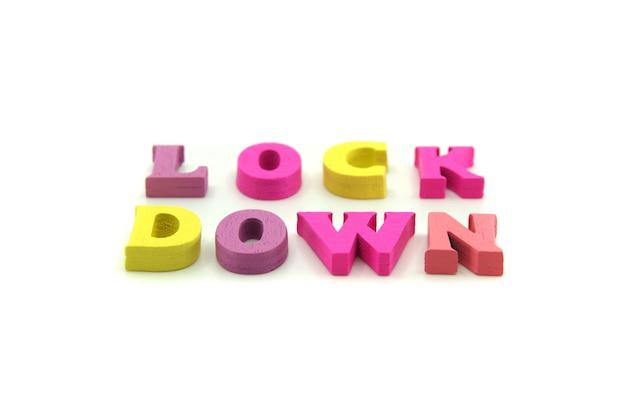 Blokada świata koronawirusa. słowo lockdown ułożone z drewnianych liter na białym tle.