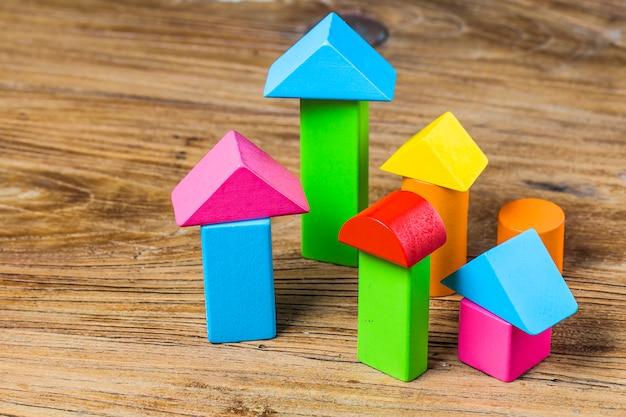 Bloki konstrukcyjne na drewnianym tle, kolorowe drewniane klocki