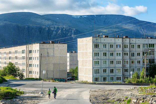 Blokuj domy budownictwa radzieckiego w pięknych górach na tle błękitnego nieba. rosyjska północ