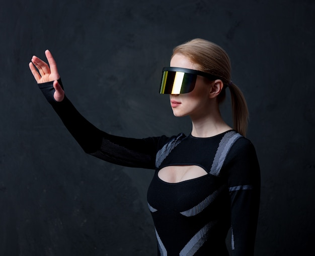 Blond android kobieta w okularach vr i garniturze na ciemnym tle.
