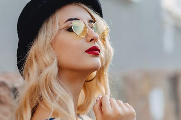Blond atrakcyjna dziewczyna w okularach przeciwsłonecznych i elegancki kapelusz przy lato światłem słonecznym miastowym