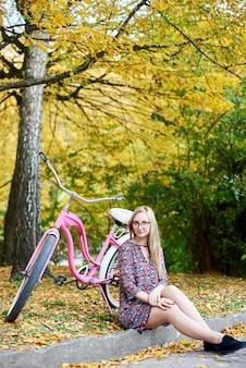 Blond atrakcyjna kobieta siedzi samotnie na ziemi przy różowym dama bicyklem pod wysokim drzewem z złotymi liśćmi na pięknym kolorowym jesieni ulistnienia wieczór