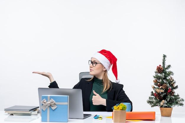 Blond biznesowa kobieta z czapką świętego mikołaja siedzi przy stole z choinką i prezentem na nim, robi ok gest i wskazuje coś po prawej stronie w biurze na białym tle