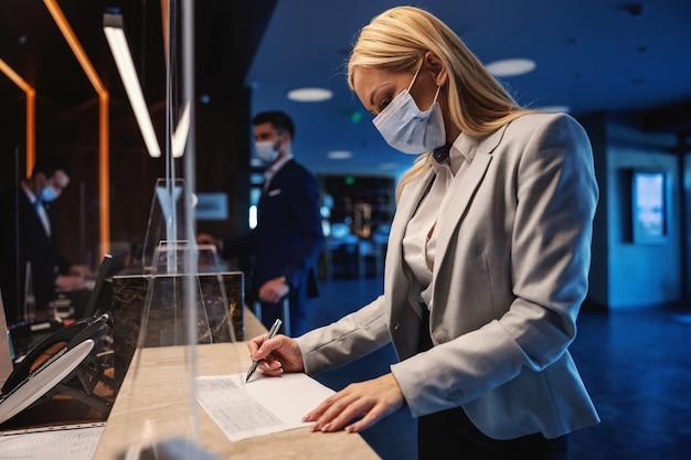 Blond bizneswoman z maską stojącą w recepcji w hotelu i wypełniając formularz podczas pandemii wirusa koronowego. podróż służbowa, podróż podczas korony, środki ostrożności dotyczące covid19