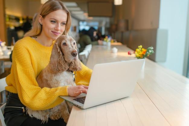 Blond blogerka freelancer w żółtej bluzie za pomocą laptopa w przestrzeni roboczej i trzymając swojego starego psa cocker spaniel na kolanach
