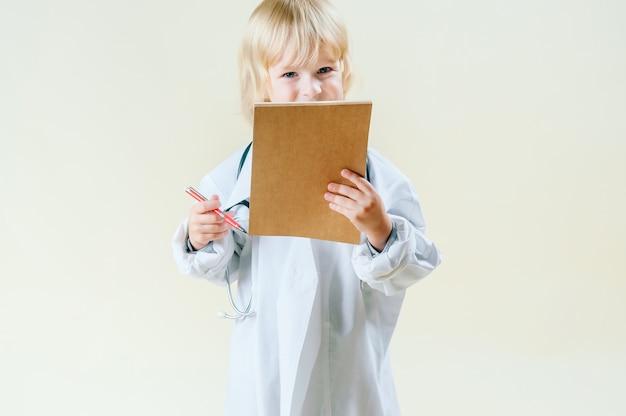 Blond blond chłopiec w ubrania lekarza