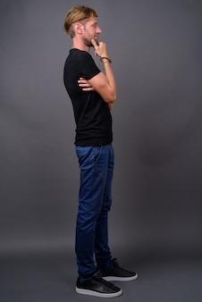 Blond brodaty mężczyzna ubrany w czarną koszulę na szaro
