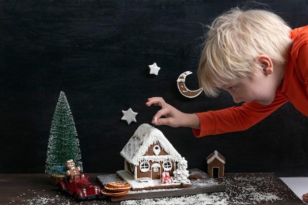 Blond chłopiec bawi się piernika. autko i choinka. tradycyjne pieczenie