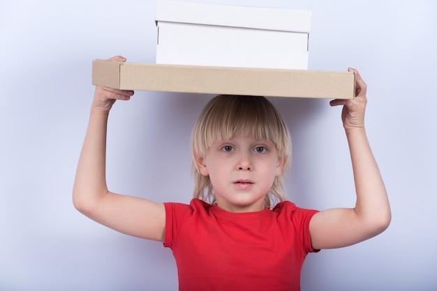 Blond chłopiec chwytów pudełko na jego głowie na biel ścianie. dostawa posiłków do domu