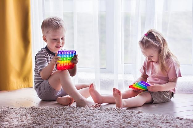 Blond chłopiec i dziewczynka dzieci bawią się zabawką sensoryczną pop it. modna gra w kręcenie silikonem dla zestresowanych dzieci i dorosłych. miękkie zabawki z bąbelkami. dziecko bawiące się kolorem tęczy pop-it