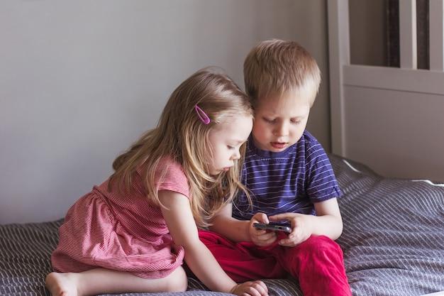 Blond chłopiec i dziewczynka siedzą na łóżku i patrzą na smartfona komunikacja online komunikacja wideo edukacja