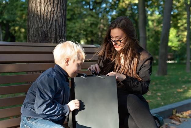 Blond chłopiec i jego niania, patrząc w torbę na zakupy, siedząc w parku. szczęśliwa rodzina.