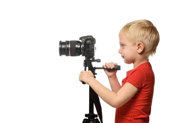 Blond chłopiec kręci wideo aparatem dslr