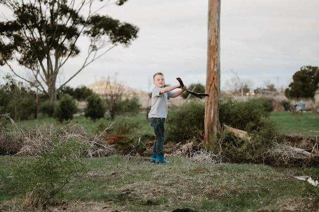 Blond chłopiec łamiący gałąź drzewa na dwie części na drewno opałowe w przyrodzie