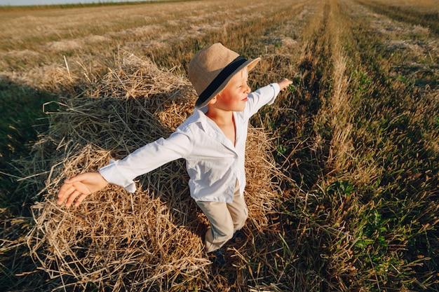 Blond chłopiec ma zabawę skacze na sianie w polu. lato, słoneczna pogoda, rolnictwo. szczęśliwe dzieciństwo. wieś.