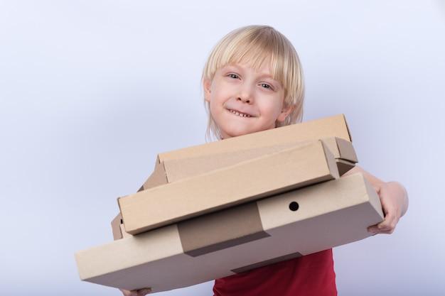 Blond chłopiec mienia pizzy pudełka na białym tle. dostawa posiłku do domu koncepcji.