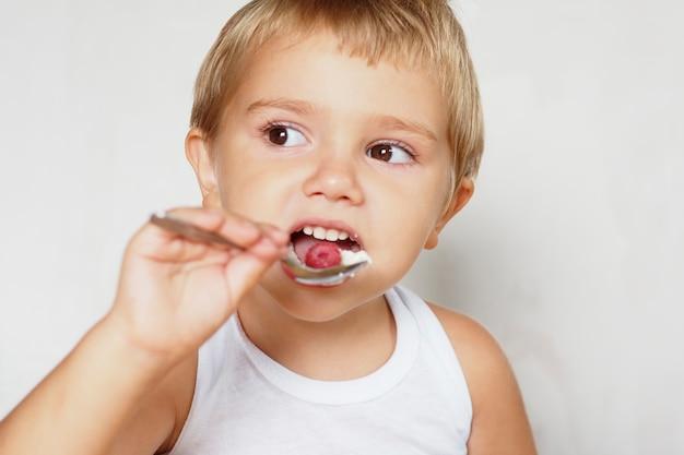 Blond chłopiec o brązowych oczach w białej koszulce zjada twarożek z jagodami przy drewnianym stole.