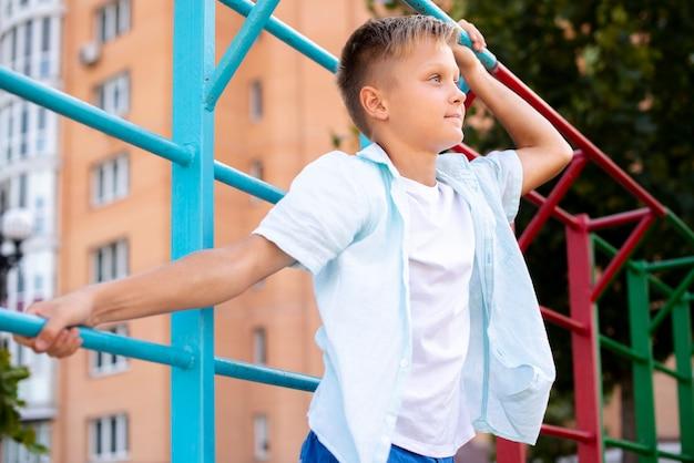 Blond chłopiec patrzeje oddalonego środka strzał