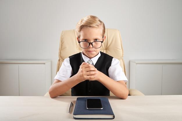 Blond chłopiec rasy białej siedzi w biurze i udając, że jest wykonawczy