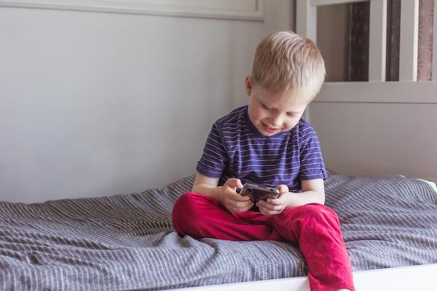 Blond chłopiec siedzi na łóżku i trzyma w dłoniach smartfon komunikacja wideo komunikacja online edukacja