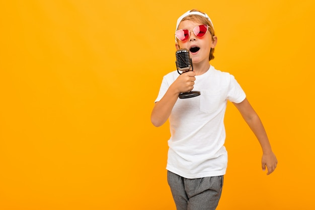 Blond chłopiec śpiewa do mikrofonu na pomarańczowej ścianie