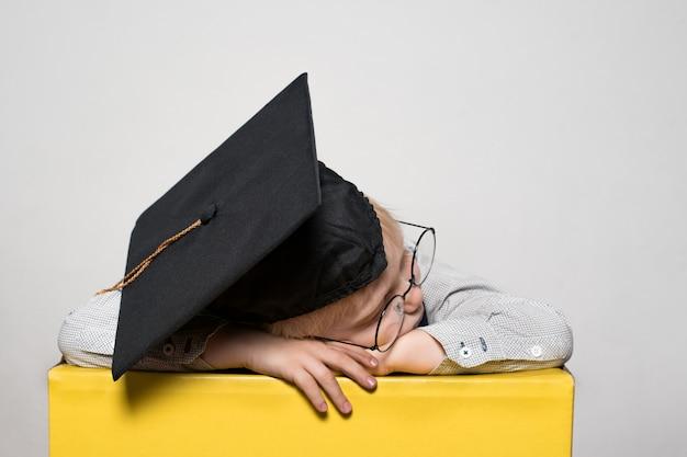 Blond chłopiec w akademickim kapeluszu i okularach śpi na stole