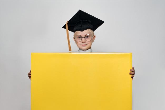 Blond chłopiec w akademickim kapeluszu i okularach trzyma duże pudełko. białe tło. koncepcja szkoły