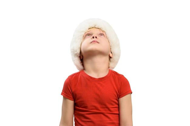 Blond chłopiec w santa hat patrzy w górę. izolować