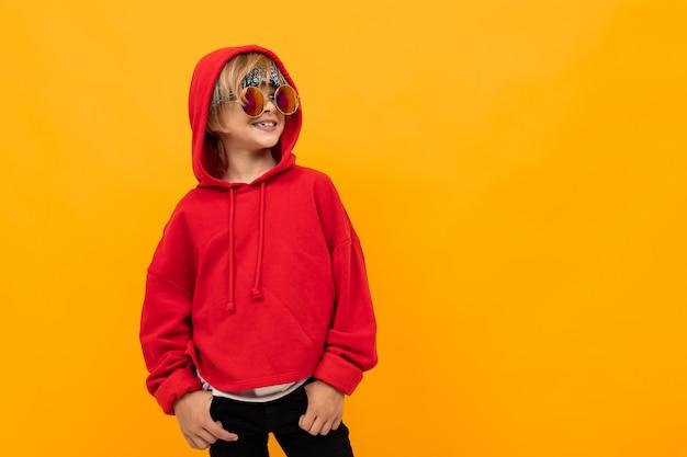 Blond chłopiec z chustką na głowie w czerwonej bluzie i szkłach pozuje na kolorze żółtym