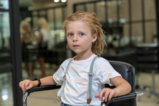 Blond chłopiec z mokrymi włosami siedzi na krześle w salonie fryzjerskim