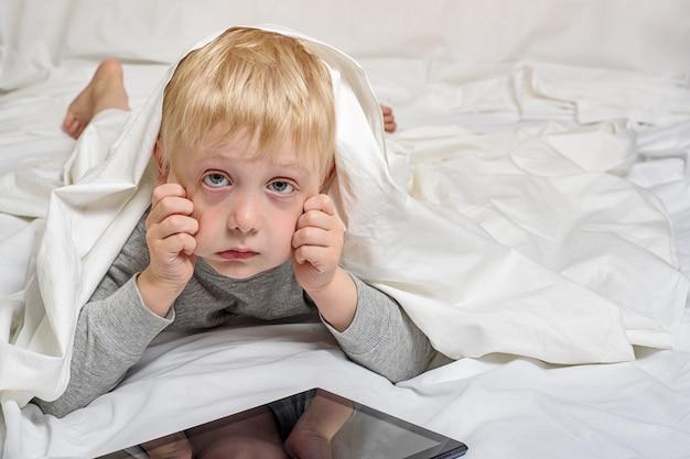 Blond chłopiec z zmęczonymi oczami od pastylki. leżąc w łóżku i chowając się pod kołdrą. gadżet wypoczynek